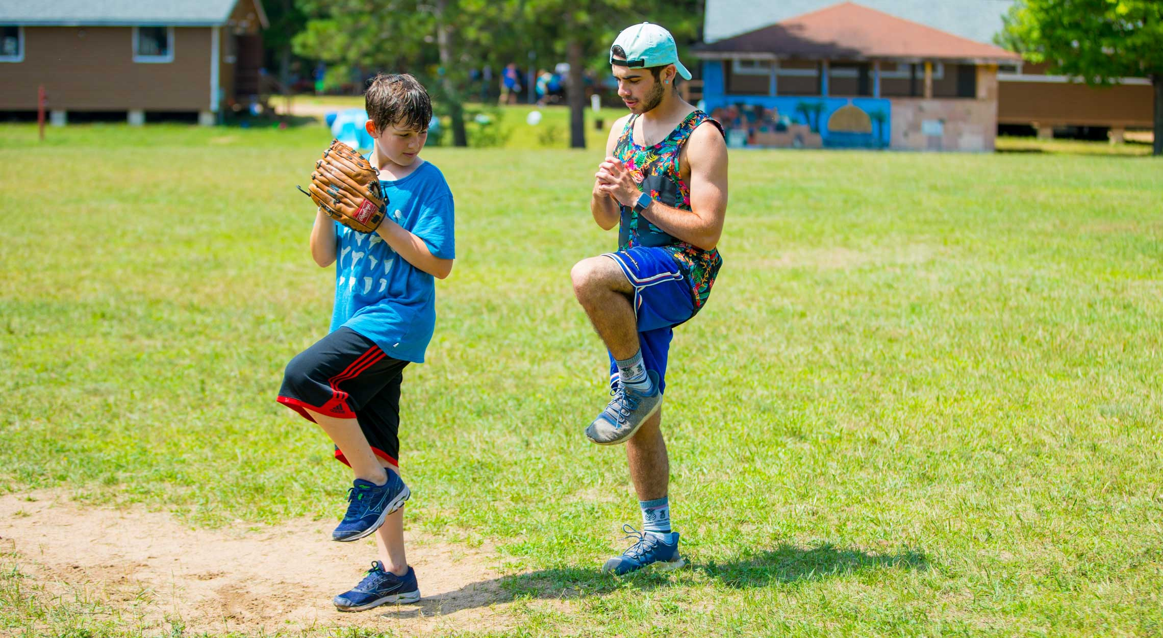 Baseball instructor teaching camper how to throw