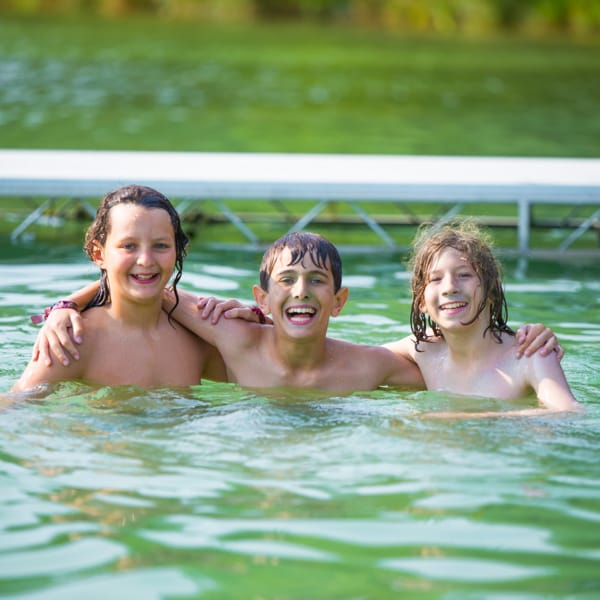 Three boys swimming in lake