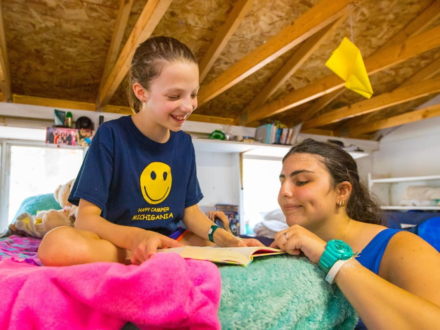 Camper and staff reading in girls bunk
