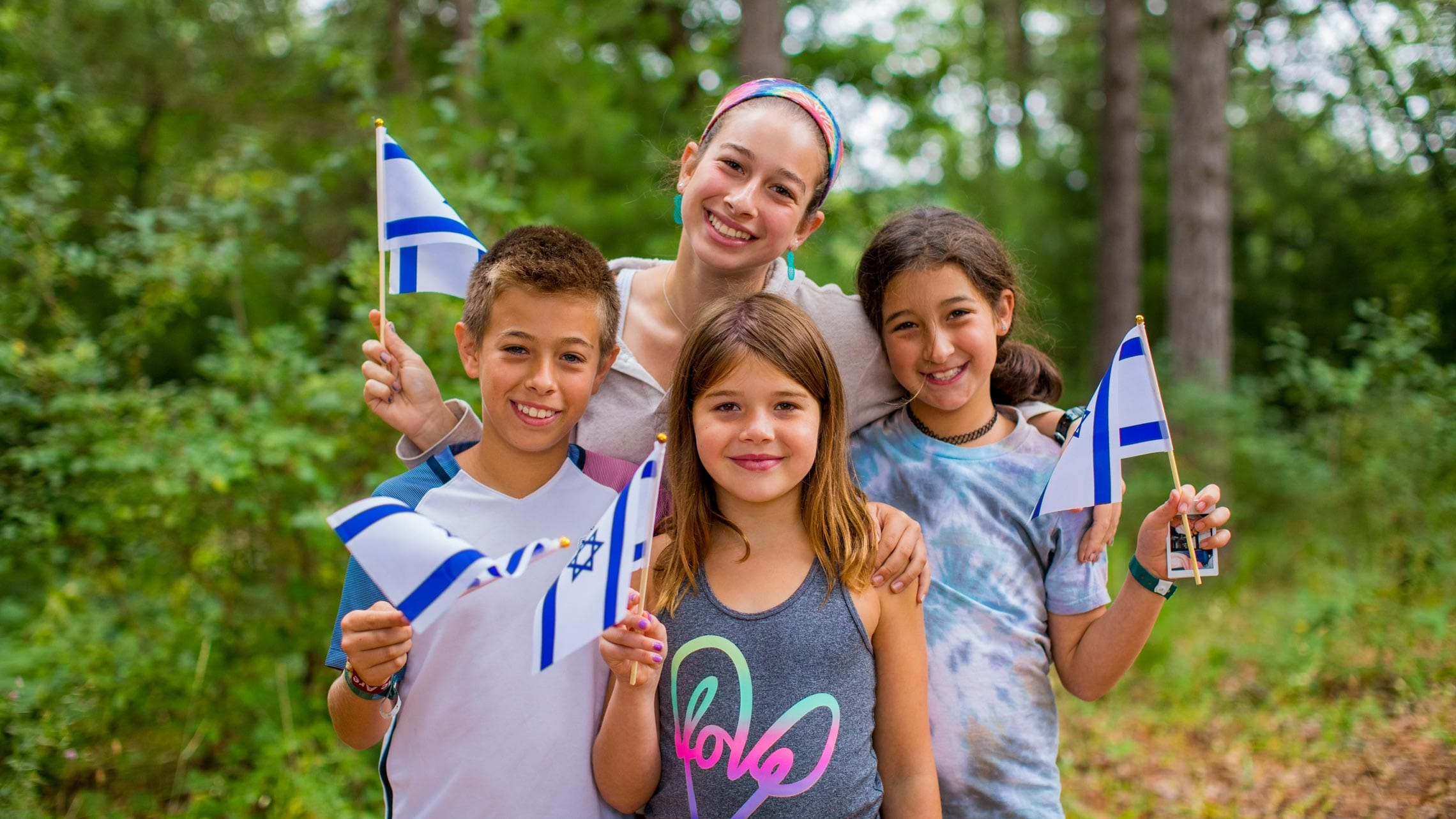 Staff and three campers with Israeli flags