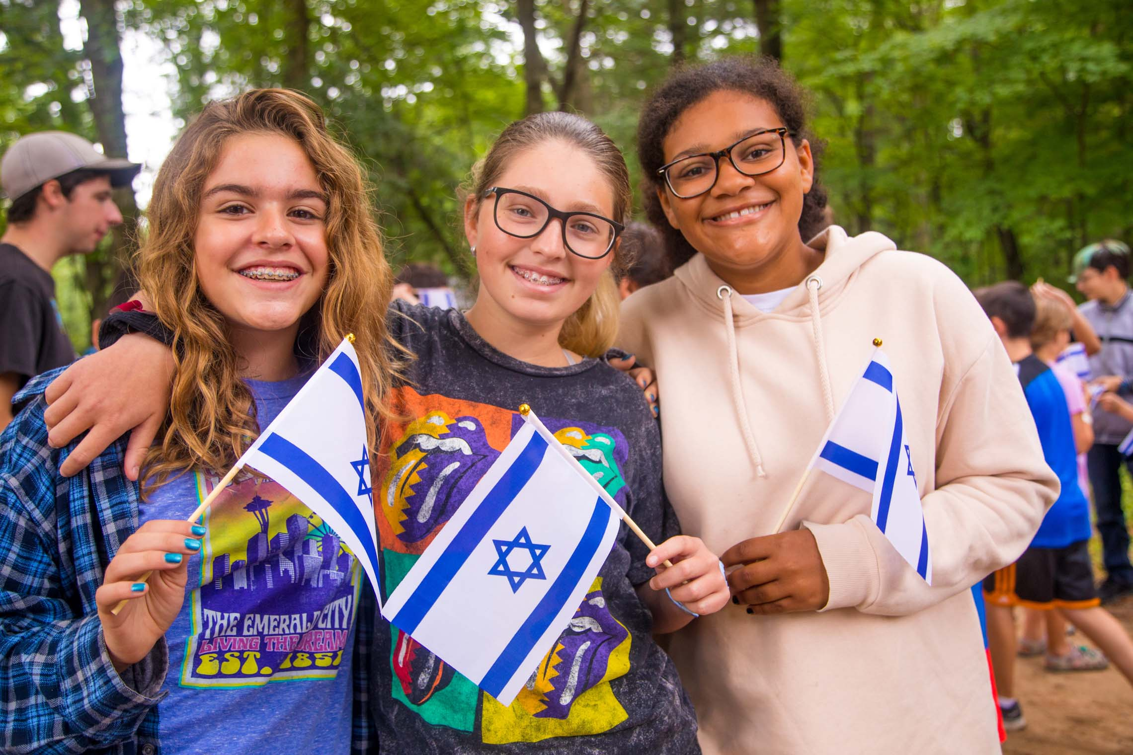 Three female campers holding Israeli flags
