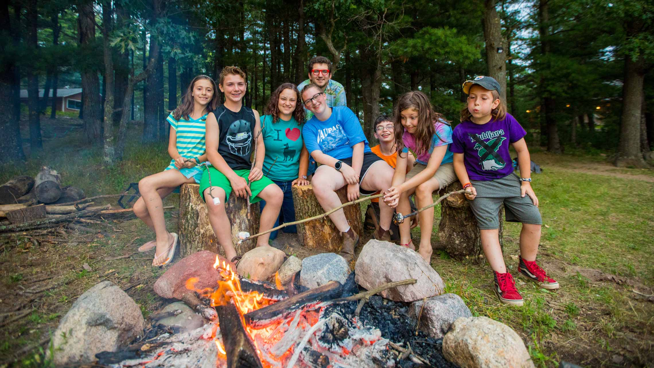 Campers roasting marshmellows by campfire
