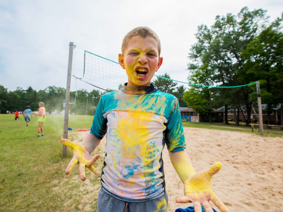 Boy covered in yellow color war powder by sand volleyball court
