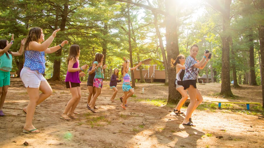 Female campers taking a dance class outdoors