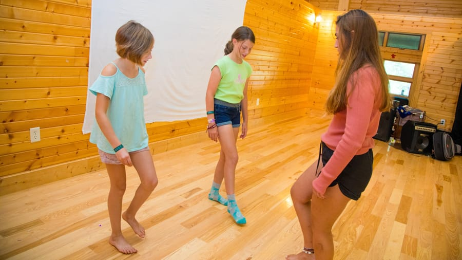 Dance instructor teaching campers footwork in dance studio