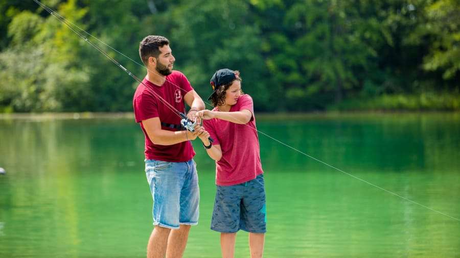Male camper and staff fishing in lake