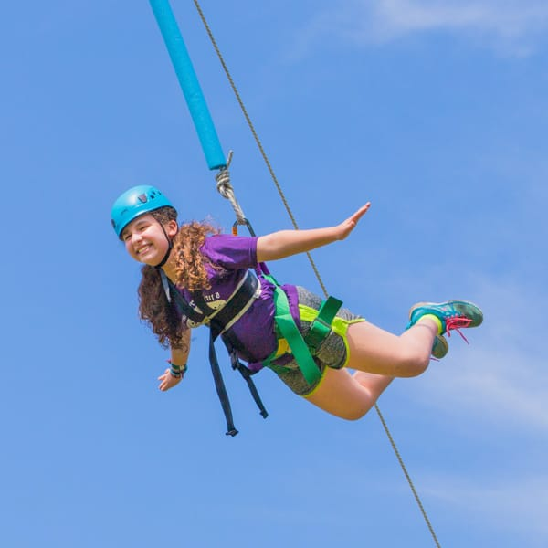 Girl on high ropes course pretending to fly