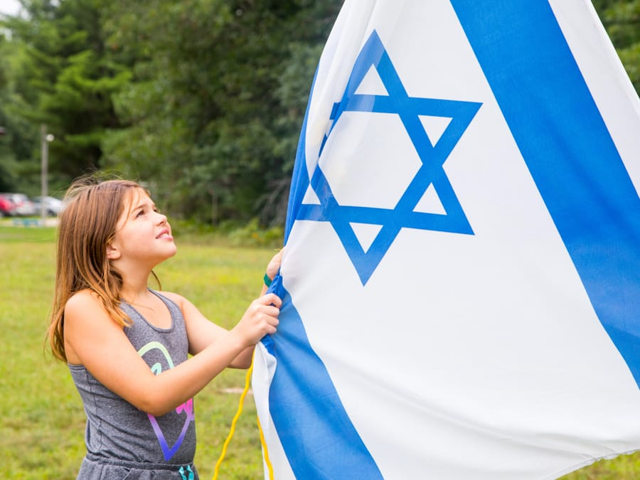 Girl getting ready to raise Israeli flag
