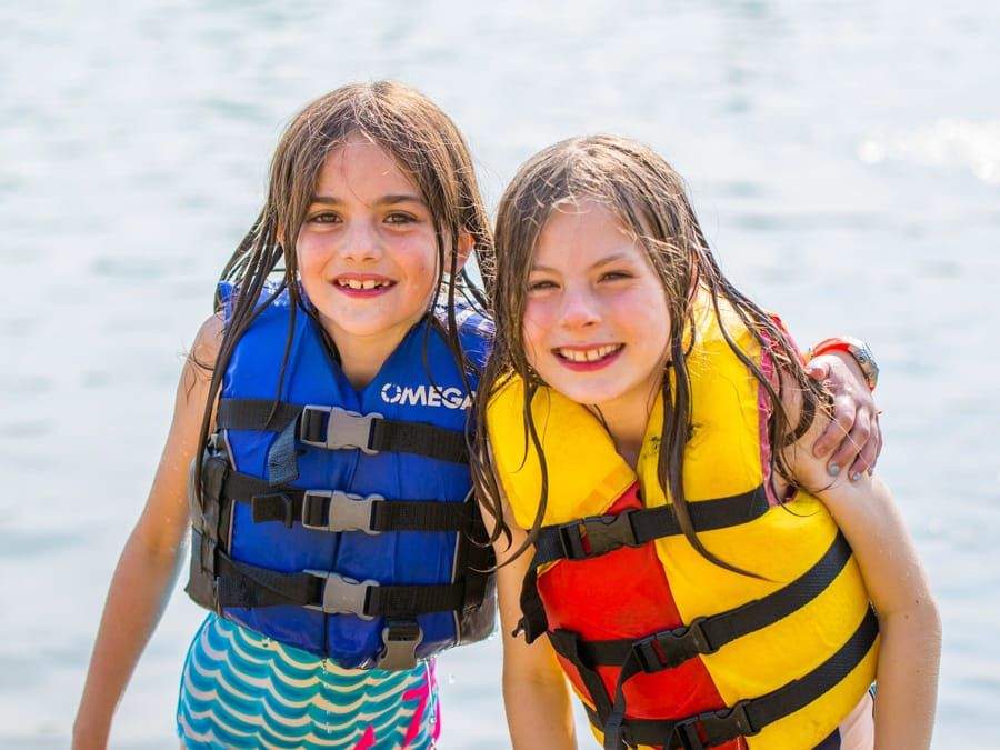 Two young girls wearing life jackets by lake