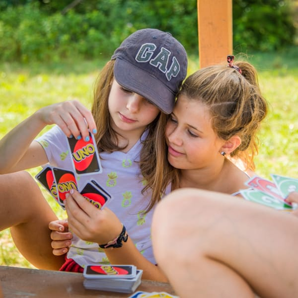 Two female campers playing Uno