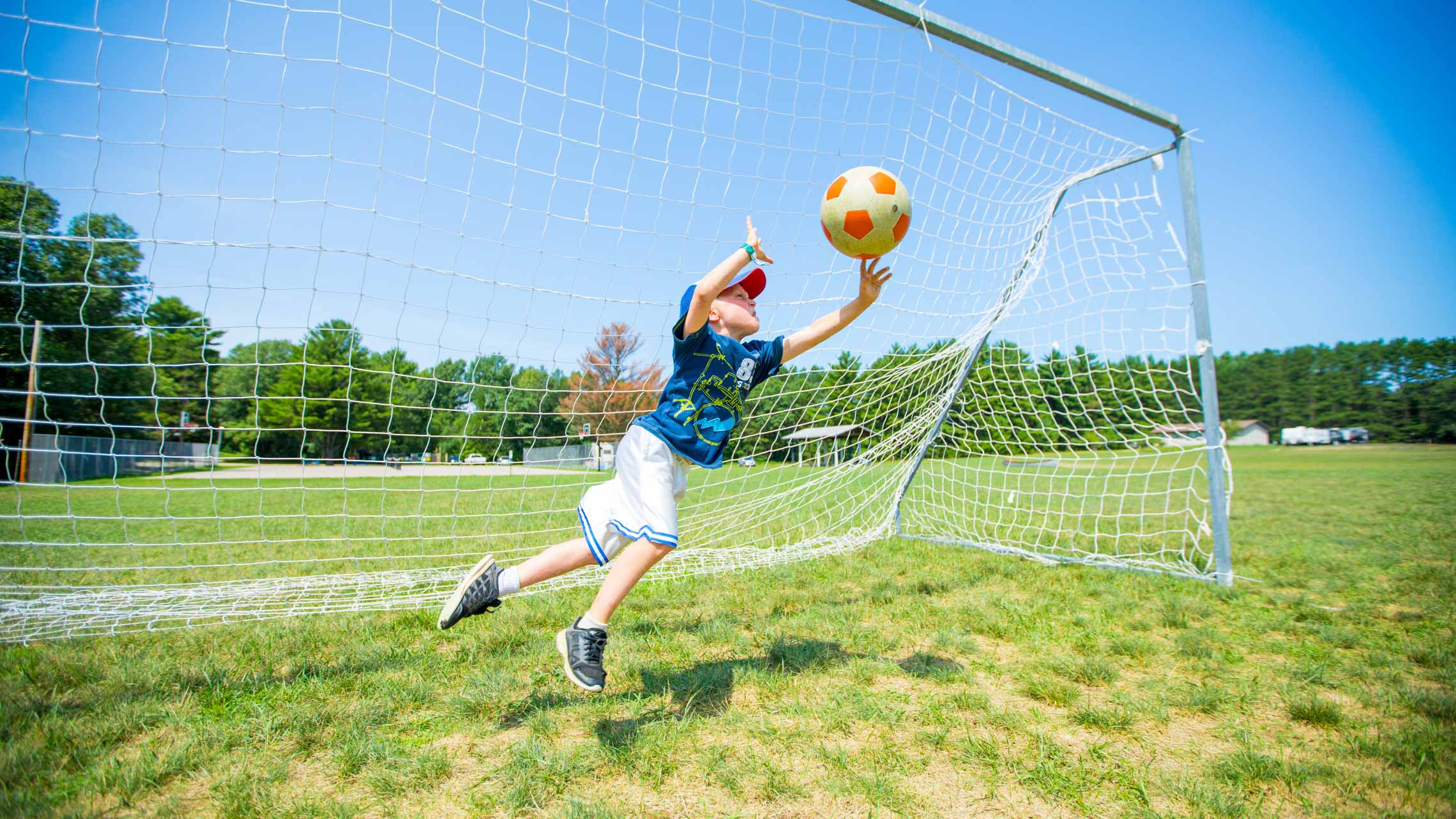 Goalie diving for soccer ball