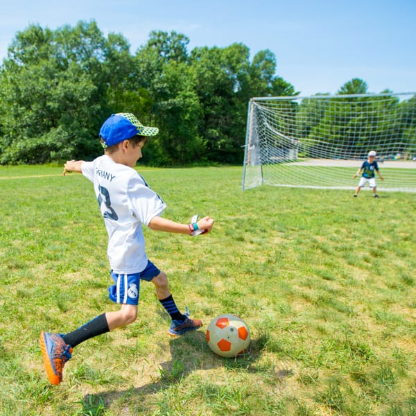 Camper kicking soccer ball towards goal