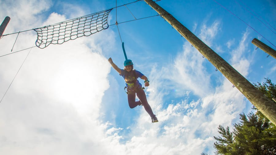 Female camper doing a Superman pose on high ropes course
