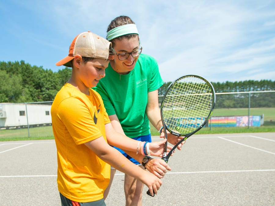 Tennis instructor teaching male camper how to hold racket