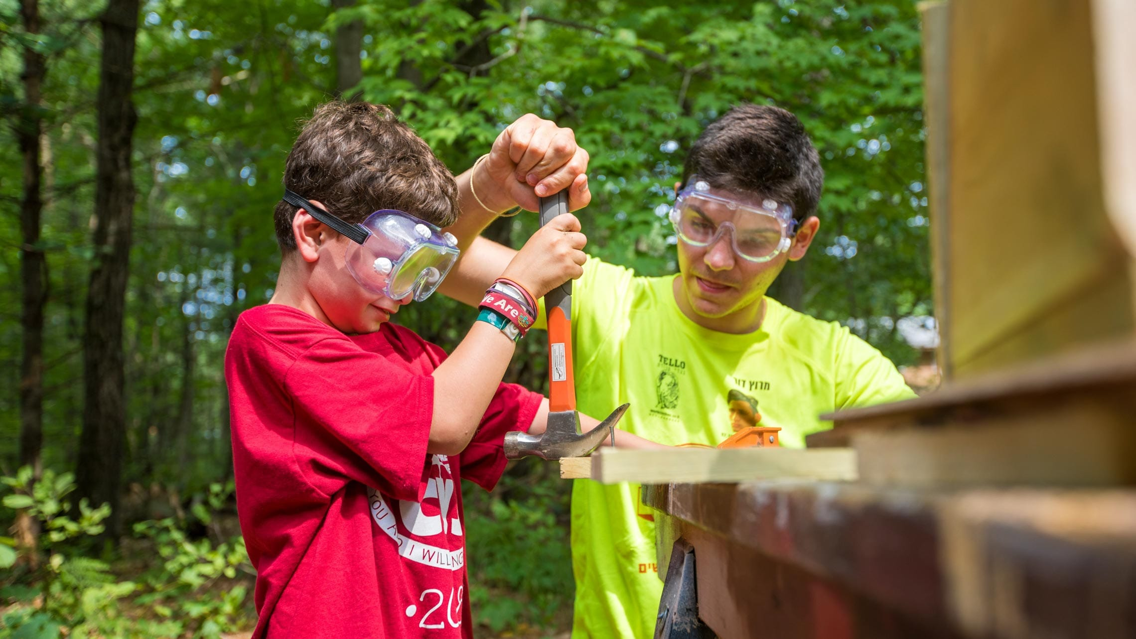 Young boy learning how to use a hammer in woodworking activity